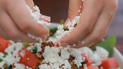 Female chef's hands spread feta cheese on watermelon vegan fruits salad
