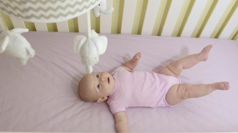 Adorable Newborn Baby Girl in Crib Looking Up at Mobile Overhead