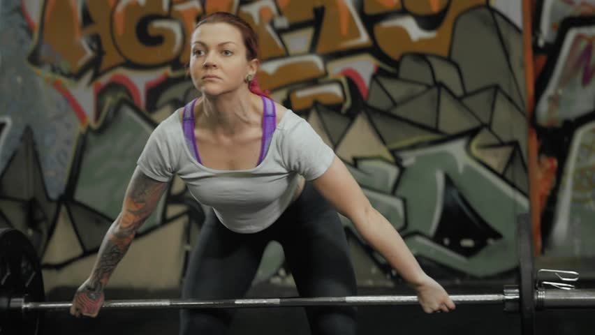 Portrait of Female performing deadlift exercise with weight bar. Confident young woman doing weight lifting workout barbell at crossfit gym. | Shutterstock HD Video #25304186
