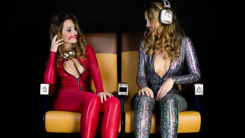 same model filmed twice interacting with herself, as a drunk out of control sexy party woman still dancing at the end of a big night out