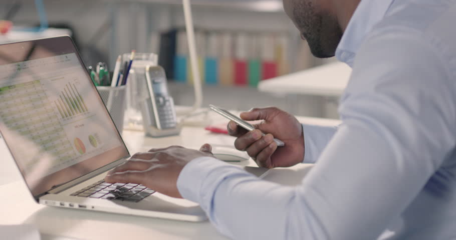 Man typing on laptop and using phone in a startup office - track left. Raw version available on request. | Shutterstock HD Video #25328321