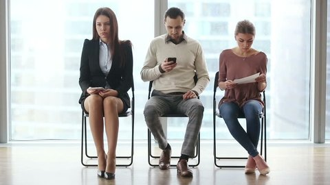 Group of three young casual people candidates sitting on chairs in modern office lobby, waiting too long for job interview, using technology devices, feeling nervous. Full length. Job search concept