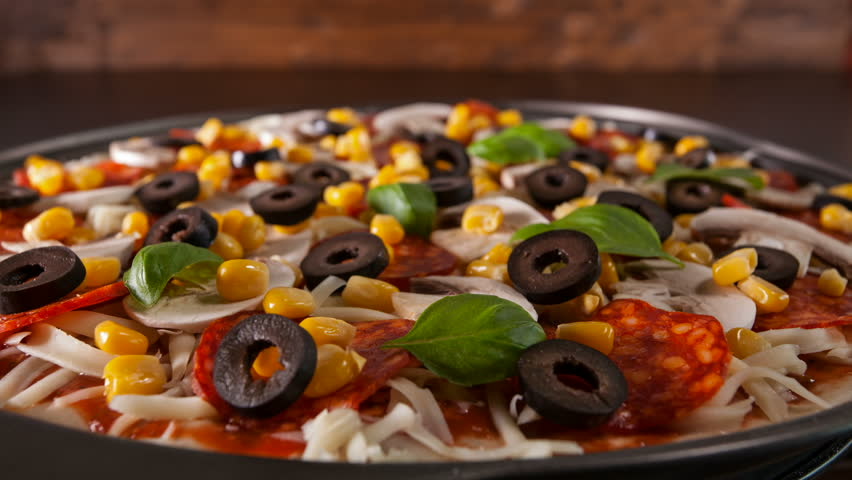 Closeup view of making a pizza with ingredients appearing on the slowly rotating baking plate - stop motion animation