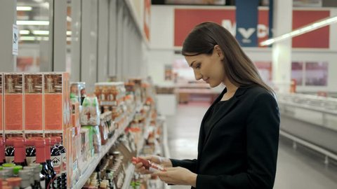 Portrait of positive woman girl buying conserve hot chilli tomato sauce or balsamic vinegar in grocery shop