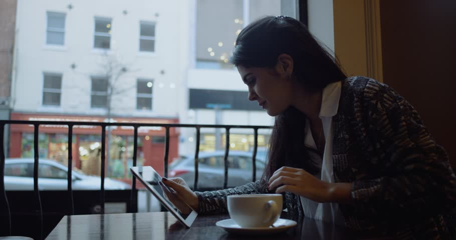 Young woman with tablet computer sitting in cafe. Slow Motion. Shot on RED Cinema Camera   Shutterstock HD Video #25354406