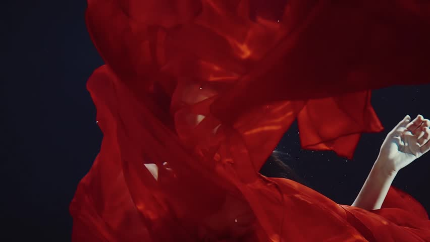 a young woman with long dark hair in a red dress swimming under water like in a fairy tale