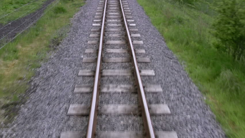 POV shot of travelling along a railway line. Fairly fast motion obtained by compressing 1 minute of footage into less than 30 seconds footage. Narrow gauge, single track in the English countryside.