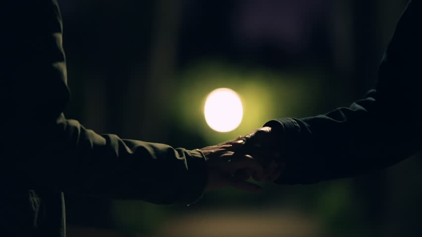 Hand to hand drug transacation at night,suspicious activity.The hands of two men do a ceremonial exchange of an illegal substance on a dark city park at night 50fps slow motion