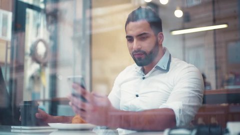 Slow motion of attractive man in the café, laughing at the internet memes, jokes. Modern life, being stylish. Texting to a friend. Close up view, camera stabilizer shot