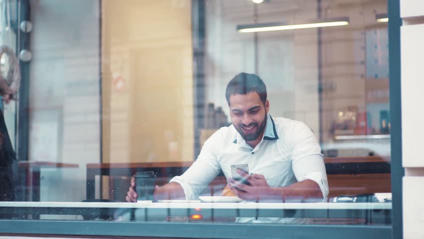 Distant view of a young businessman sitting at a table in a cafe using iphone and laughing, watching the passersby. Successful people, daily routine. Entertaining, relaxing, communicating. | Shutterstock HD Video #25411766