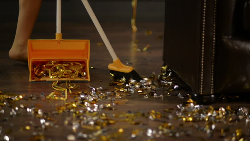 Sweeping of Golden and Silver Confetti at the End of the Party. Colorful Paper on the Floor. Closeup of Female Legs and a Broom. Housekeeping Concept.