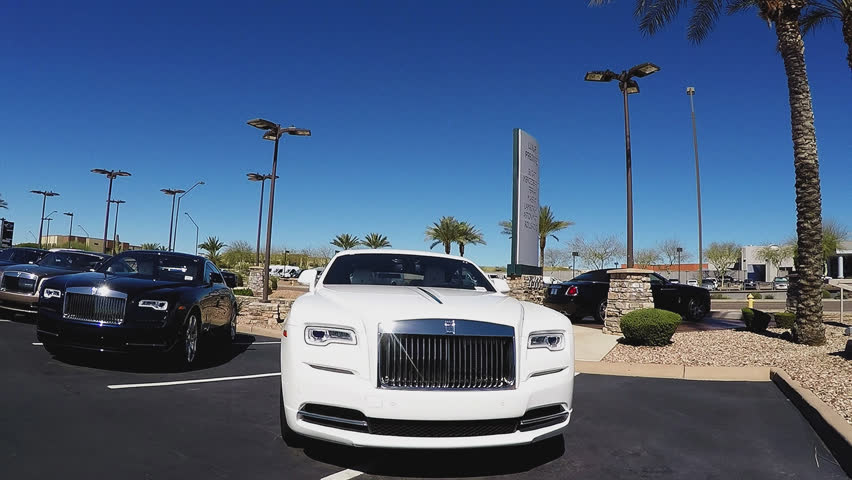 SCOTTSDALE AZ/USA: February 28, 2017- Drive by shot of shiny Bentley and Ferrari luxury cars at a dealership. Clip reveals row of expensive import vehicles in a automotive car lot.