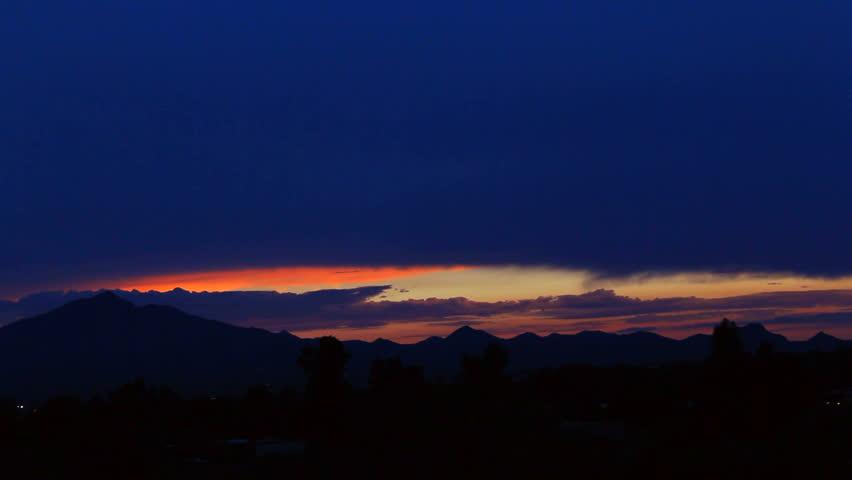 Darkness descends as last beams of sun light sky orange, red, yellow. 1080p