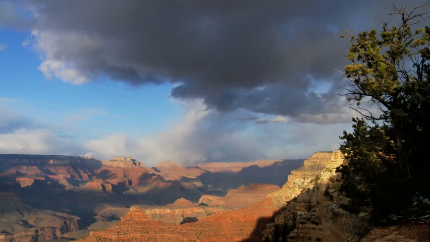 Scenic Grand Canyon at sunset with dramatic clouds, red cliffs and blue skies