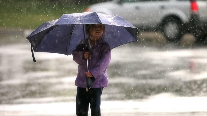 Little girl holding an umbrella in the rain
