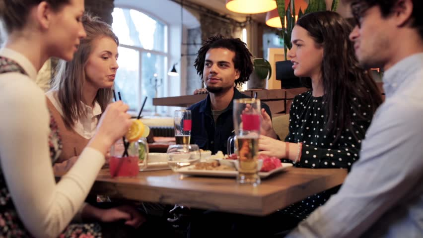 Leisure, food, drinks, people and holidays concept - happy friends eating and drinking at bar or cafe | Shutterstock HD Video #25542296