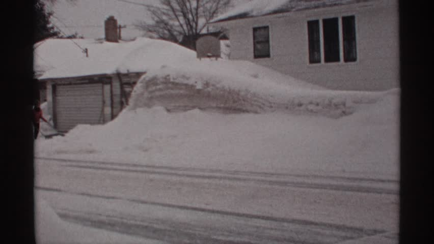 WISCONSIN 1971: someone is plowing snow by hand amidst a snowdrift caused by winter precipitation