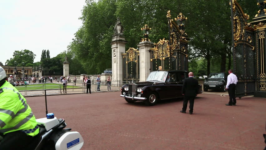 LONDON - CIRCA SUMMER 2012: Prince Charles and Camilla pass by the Buckingham Palace in their Royal Rolls Royce in London, England in the Summer of 2012.