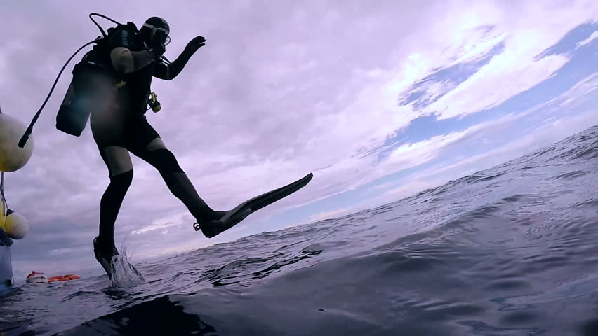 Scuba Diver Jumping into the Ocean. In slow motion a scuba diver jumps into water.  Scuba Diver Jumping Off Dive Boat. | Shutterstock HD Video #25565063