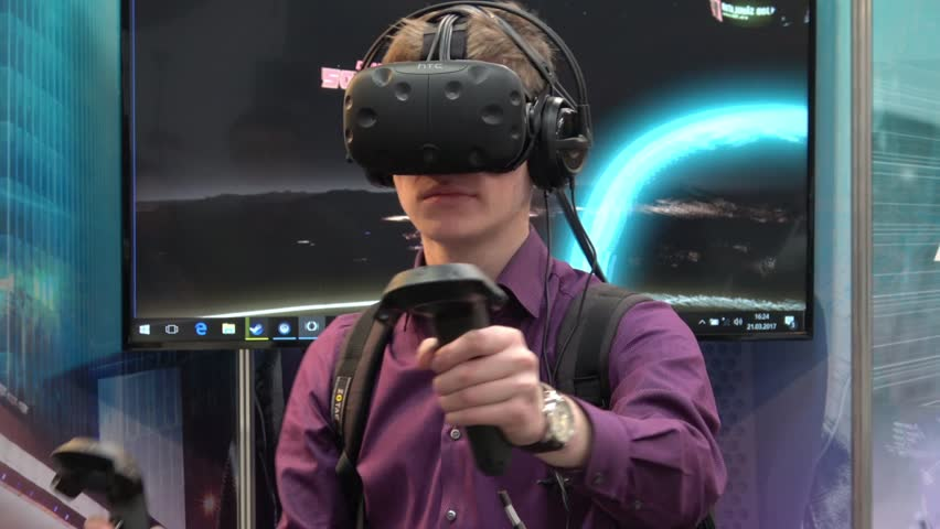 Hannover, Germany - March, 2017: Man playing video game in virtual reality headset and handheld controllers developed by HTC Vive on exhibition Cebit 2017 in Hannover Messe, Germany | Shutterstock HD Video #25567316