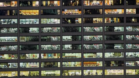Timelapse of office workers activity in the windows of skyscraper after sunset at evening time