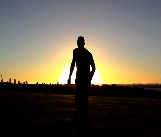 A youth jumps against the backdrop of a setting sun.