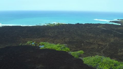 Aerial shot starting from a small green oasis and pond, pulling back to reveal stark lava rock fields and the bright blue Pacific Ocean and hazy Big Island sky, Kona, Hawaii.