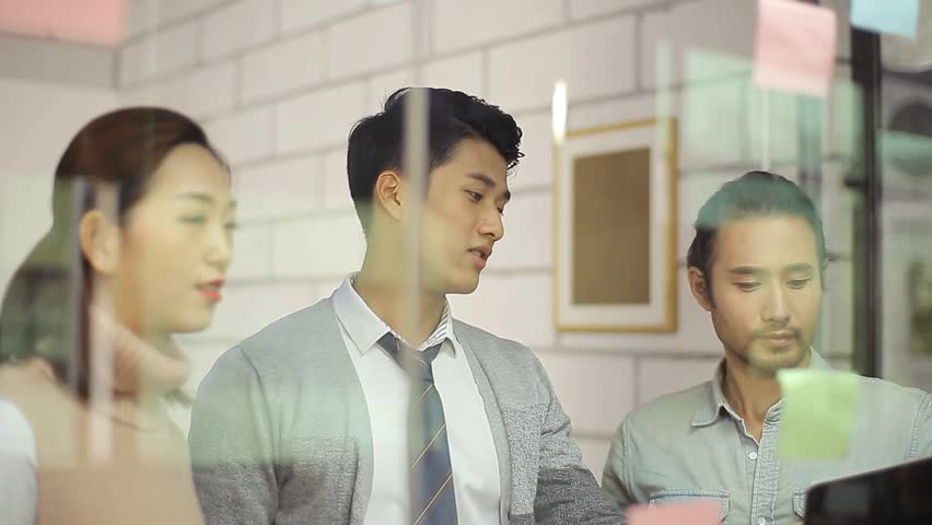 Team of corporate people discussing business situation using sticky note in glass meeting room in office.  | Shutterstock HD Video #25601495
