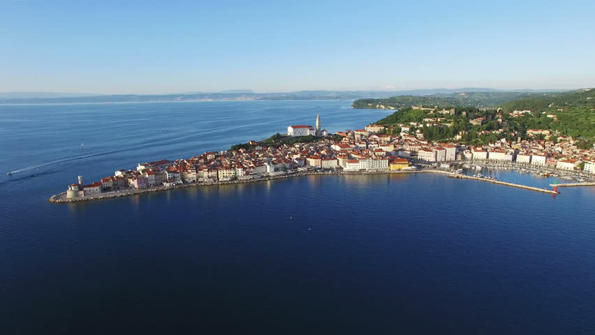 Flight over old city Piran in Slovenia, aerial panoramic view with old houses, St. George's Parish Church, Tartini Square, fortress and the sea.