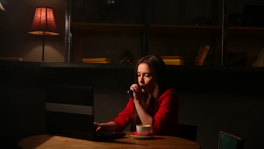 Girl working with laptop drinking coffee Smoking an electronic cigarette. Working remotely in a cafe. | Shutterstock HD Video #25627406