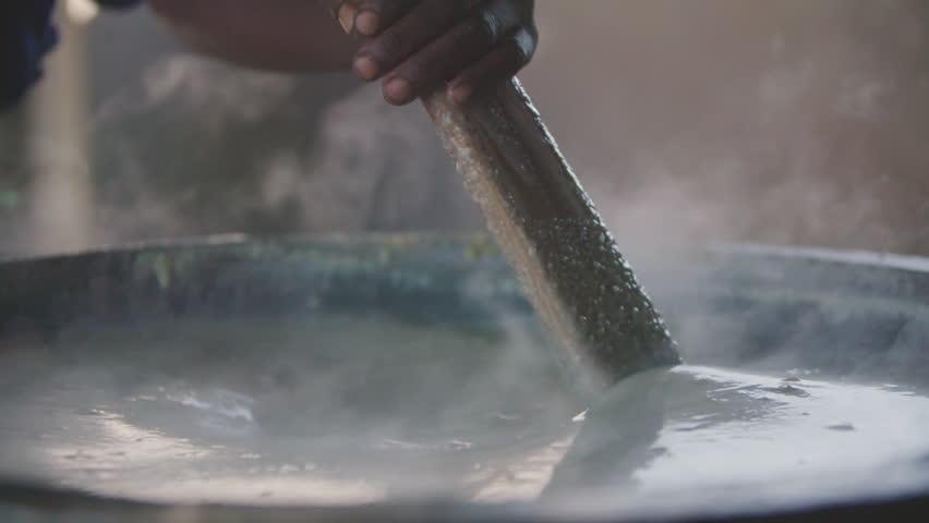 Malawi - November 2016: Woman stirring large pot of porridge at a school