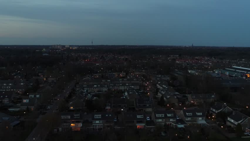 Aerial view night flight over residential district suburbs showing the neighborhood typical family houses and small lights from the homes and architecture at evening time very stable flight 4k
