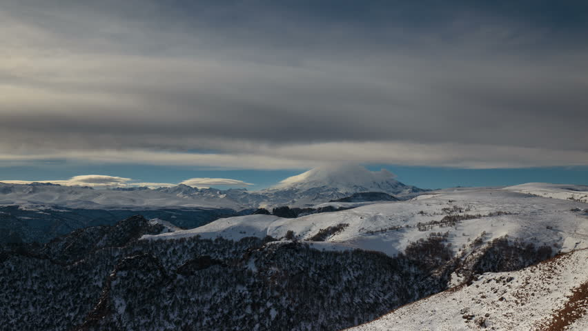 Russia, timelapse. The formation and movement of clouds above the volcano Elbrus in the Caucasus Mountains in winter. #25655336