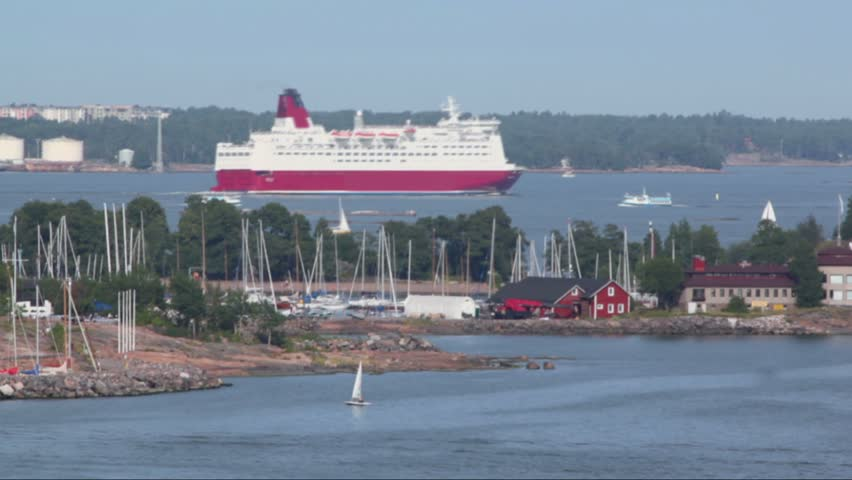 Huge liner among smaller vessels float near coastline beside Helsinki