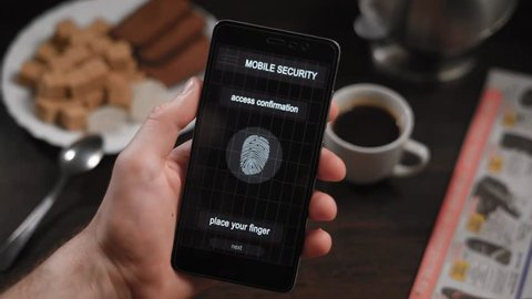 Secure and quick access to your account with fingerprint scanning. The application on the smartphone, the man applies his finger to the scanner, the program allows access.