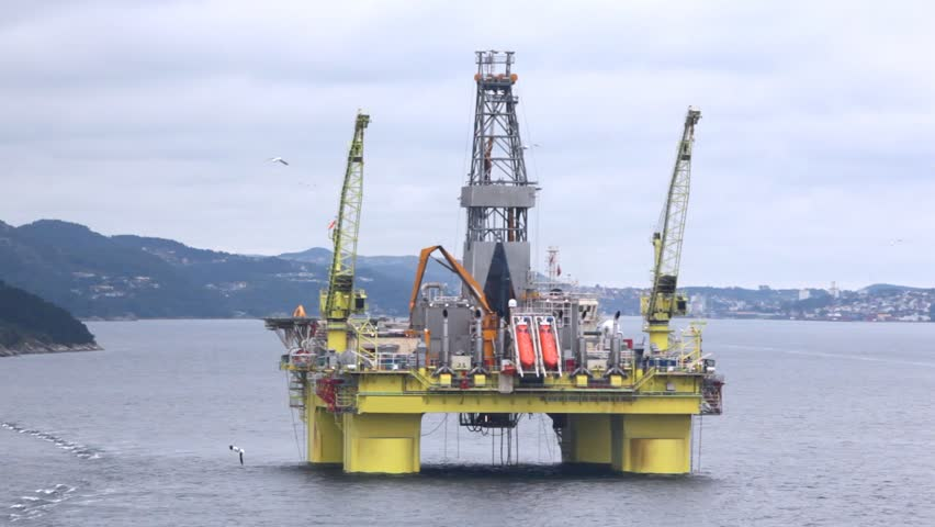 Drilling platform Coslpioner stands in Stavanger gulf against mountains