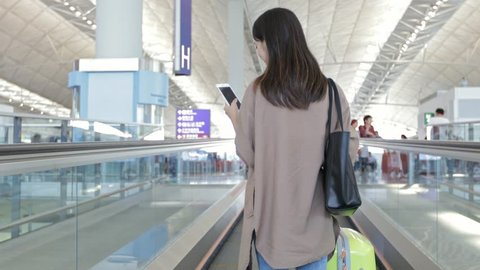 Back view of woman on travelator and using cellphone with her luggage at Hong Kong international airport