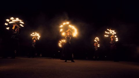 Fire show. A group of professional artists performs a variety of fire facilities. Boys and girls performed dances with fire in the night on the street in the Park
