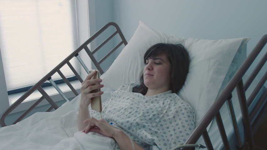 A sick young woman with an IV texting on a smartphone in a hospital bed next to a window, slow motion