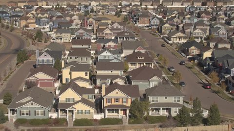 AERIAL CLOSE UP Flying above the rooftops of new modern expensive row houses in subdivision, Denver, America. Luxury real estates with frontyards in quiet suburban community on tranquil sunny fall day