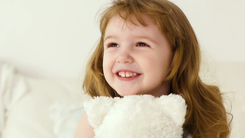 Redhead girl with long hair two years of hugs white Teddy bear | Shutterstock HD Video #25794386