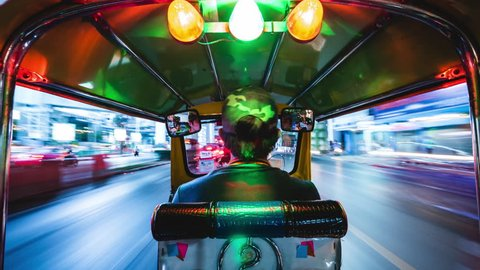 Bangkok, Thailand - March 21: Tuk tuk ride motion time lapse at night in Bangkok, Thailand. Tuk-tuks are a popular means of transportation in Southeast Asia.