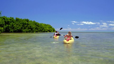 Couple Kayaking off Tropical Island