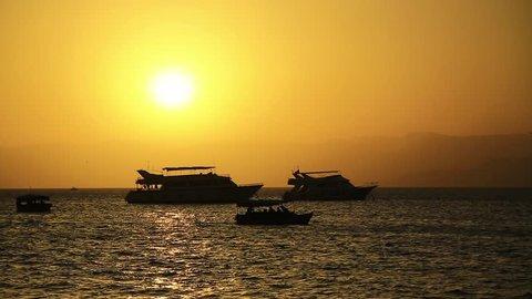 Ships in sea near Aqaba city, Hashemite Kingdom of Jordan. Red Sea, Gulf of Aqaba. Silhouettes of ships in the sea at sunset