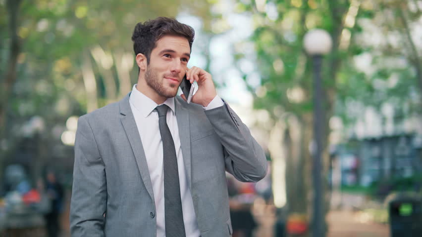 Attractive and cheerful young businessman using a cell phone in a city park. He is checking mails, chats or the news online.  | Shutterstock HD Video #25833551