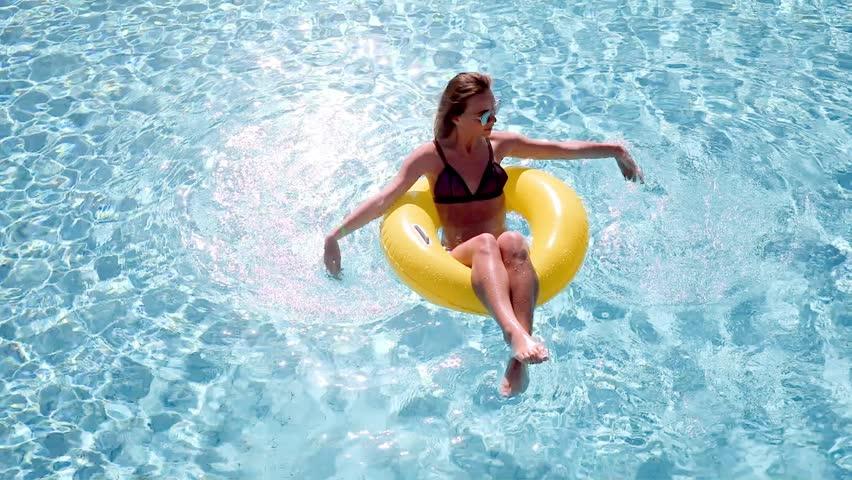Sexy woman in bikini enjoying summer sun and tanning during holidays in pool . Top view. Woman in swimming pool. Sexy woman in bikini.