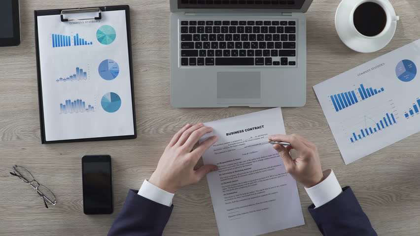 Head of department reading business contract attentively, top view of workplace   Shutterstock HD Video #25845332