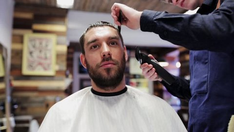 beauty, hairstyle and people concept - man and stylist or hairdresser with trimmer doing haircut at hair salon or barber shop