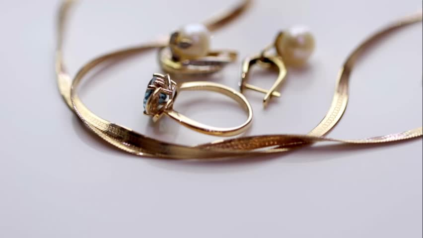 Gold ring with Topaz and pearl earrings on a rotating stand