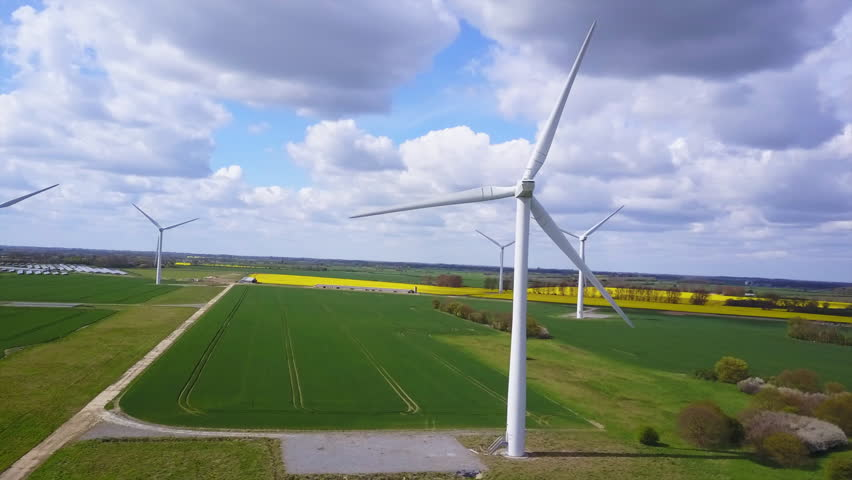 Stunning Sweeping Aerial Shot of  Wind Turbines on a Sunny Cloudy Day